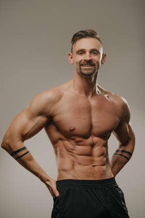 A smiling muscular man with a beard is posing. The athletic guy is squeezing his muscles. A bodybuilder with tattoos on his forearms is standing with his hands on his hips Standard-Bild