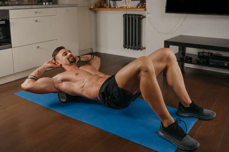 A muscular man with a naked torso is doing a myofascial massage to himself with a roller on a yoga mat in his apartment. A bodybuilder with tattoos on his forearms is training at home.
