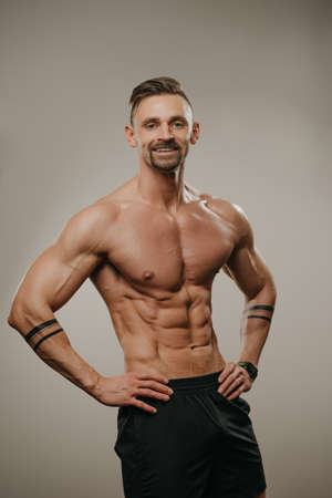 A smiling muscular man with a beard is posing. The athletic guy is demonstrating his sporty physique. A bodybuilder with tattoos on his forearms is standing with his hands on his hips