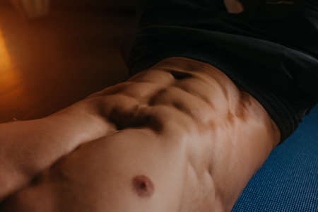 A close photo of a bodybuilder's abs during doing crunches on a blue yoga mat.