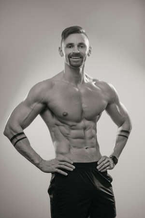 A black and white photo of a muscular man with a beard who is posing. The athletic guy is demonstrating his sporty physique. A bodybuilder with tattoos on his forearms is relaxing after hard training.