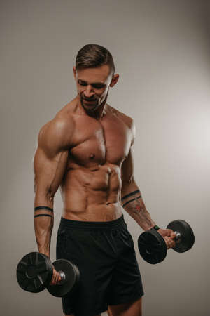 A muscular man with a beard is doing bicep curls with dumbbells. An athletic guy is demonstrating his sporty torso. A bodybuilder with tattoos on his forearms is training his arms Standard-Bild