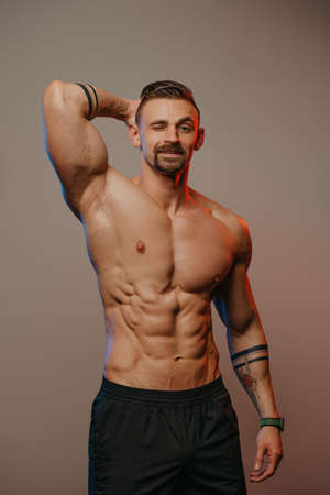 A smiling muscular man with a beard is posing. The athletic guy is demonstrating his sporty physique. A bodybuilder with tattoos on his forearms is standing with one hand behind his head