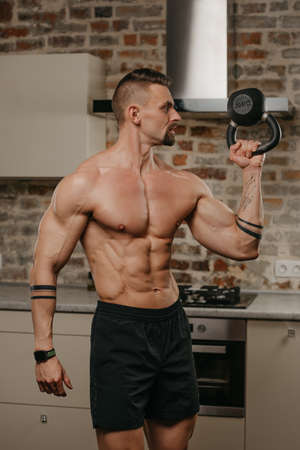 A muscular man with a beard is training biceps with a black weight in his apartment. A bodybuilder with a naked torso and tattoos on his arms is warming up during a workout at home
