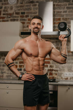 A happy muscular man with a beard is pushing a black weight in his apartment. A bodybuilder with a naked torso and tattoos on his arms is warming up during a deltoids workout at home