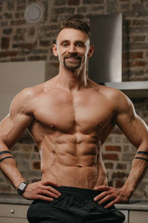 A muscular man with a beard is posing in his apartment. The athletic guy with tattoos on his forearms is demonstrating his sporty physique at home. An athlete is relaxing after hard training.