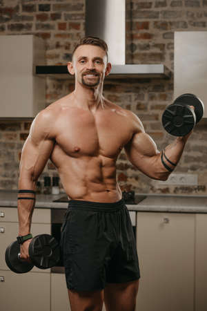 A muscular man with a beard is training his biceps with dumbbells in his apartment. A bodybuilder with tattoos on his arms is warming up during a workout at home. An athlete with a naked torso.