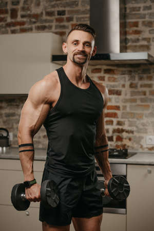 A happy muscular man with a beard is posing with dumbbells in his apartment. An athletic guy with tattoos on his arms is warming up during a workout at home. An athlete is training his biceps.