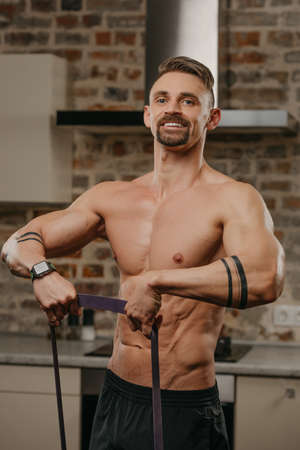 A muscular man is working out with an elastic pull rope in his apartment. Athletic guy with tattoos on his forearms is doing a deltoid muscles workout at home. A smiling bodybuilder with a naked torso