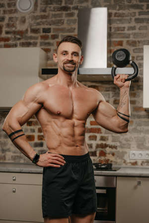 A happy muscular man with a beard is training biceps with a black weight in his apartment. A bodybuilder with a naked torso and tattoos on his arms is warming up during a workout at home Standard-Bild