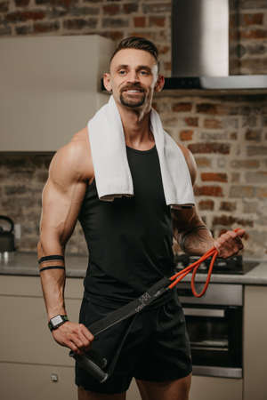 A muscular man with a white towel on the shoulders is posing with pull elastic rope in his apartment. The bodybuilder with tattoos on his forearms is demonstrating his sporty physique at home Standard-Bild