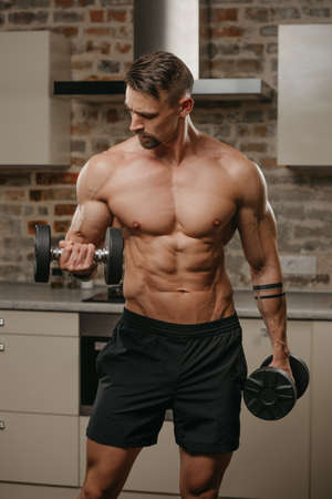 A muscular man with a beard is training his biceps with dumbbells in his apartment. A bodybuilder with tattoos on his arms is warming up during a workout at home. Athlete with a naked torso in shorts