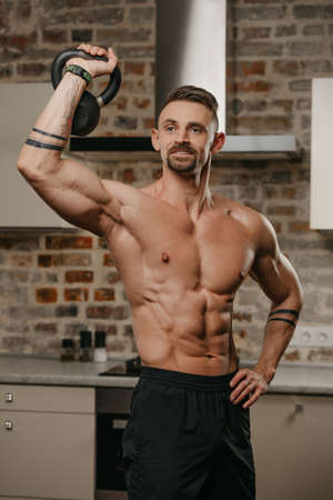 A happy muscular man with a beard is pushing a black weight in his apartment. An athlete with a naked torso and tattoos on his arms is warming up during a deltoids workout at home Standard-Bild