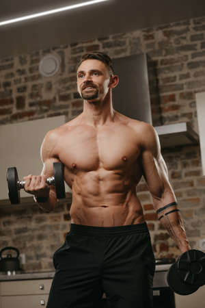 A muscular man with a beard is training his biceps with dumbbells in his apartment. A happy bodybuilder with tattoos on forearms is warming up during an arm workout at home. Athlete with a naked torso