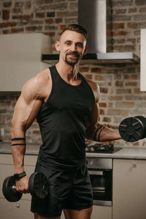 A happy muscular man with a beard is training biceps with dumbbells in his apartment. An athletic guy with tattoos on his arms is warming up during a workout at home.