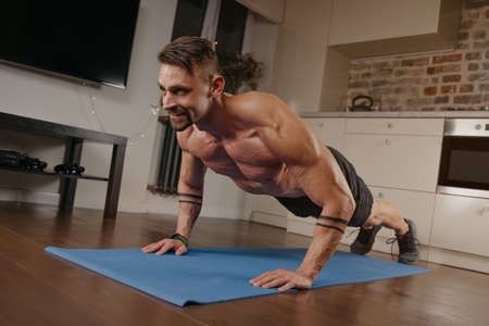 A muscular man is doing pushups on a blue yoga mat in his apartment. An athletic guy with tattoos on his forearms is doing a chest and triceps workout at home. A happy bodybuilder with a naked torso