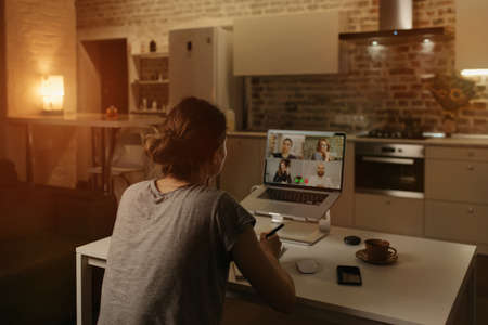 Back view of a female employee who is working remotely talking to her colleagues in a video conference on a laptop from home. A multiethnic business team on an online meeting in the evening.