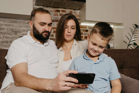 A dad, a son, and a mom are watching video on the sofa. A gloomy husband with a beard is demonstrating the show on the smartphone to a child and a wife in the evening at home.