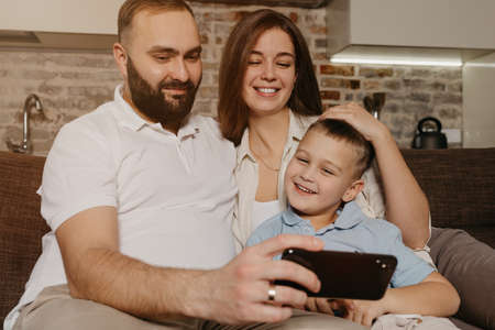 A dad, a son, and a mom are watching video on the sofa. A happy husband with a beard is demonstrating the show on the smartphone to a smiling child and a wife in the evening at home.