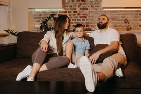Dad with a beard, son, and young mom with long hair are watching TV and smiling on the sofa. The family is enjoying a happy evening at home. A child is listening to his mother.