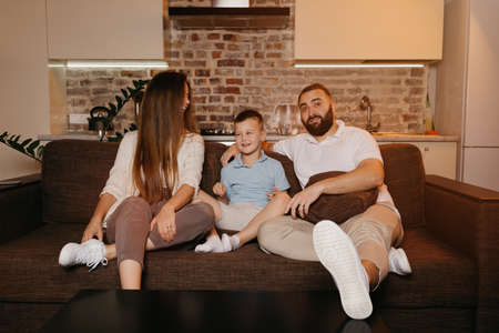 Dad, son, and mom are watching with interest TV on the sofa in the apartment. The family is enjoying a happy evening at home. The young mother with long hair is staring at her husband and laughing.