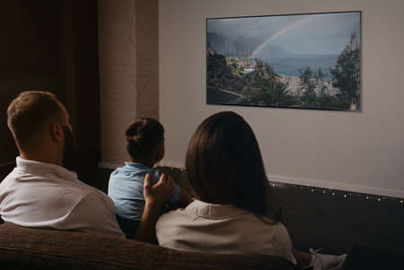 A photo from behind of a father, a son, and a young mother which are watching a movie on a widescreen television set on the sofa. The family is enjoying a video together in the evening at home.