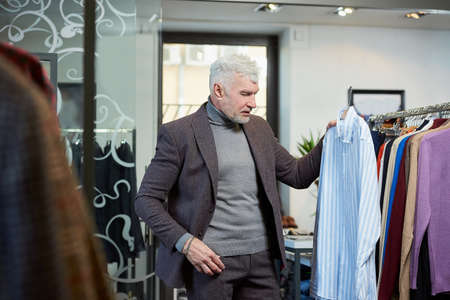 A mature man with gray hair is choosing a shirt in a clothing store. A male customer with a beard wears a wool suit in a boutique.
