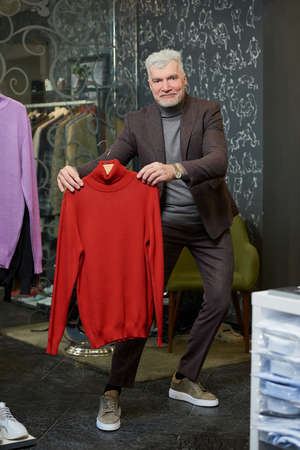 A happy mature man with gray hair is showing a red turtleneck sweater in a clothing store. A male customer with a beard wears a wool suit in a boutique. Stock Photo