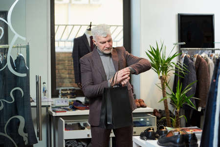 A mature man with gray hair and a sporty physique is staring at his wristwatch holding two black paper bags in a clothing store. A male customer with a beard wears a wool suit in a boutique Stock Photo