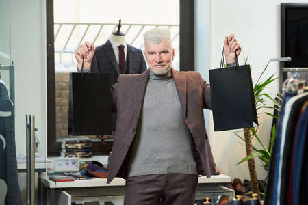 A happy mature man with gray hair and a sporty physique is showing two black paper bags with purchases in a clothing store. A smiling male customer with a beard wears a wool suit in a boutique Stock Photo