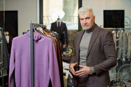 A mature man with gray hair is posing while choosing a turtleneck sweater in a clothing store. A male customer in a wool suit in a boutique. Stock Photo