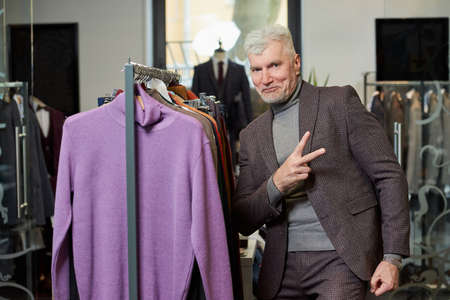 A mature man with gray hair is showing a Victory sign in a clothing store. A happy male customer in a wool suit in a boutique. Stock Photo