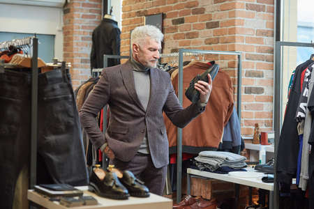 A mature man with gray hair and a sporty physique is staring at a shoe in a clothing store. A male customer with a beard wears a wool suit in a boutique