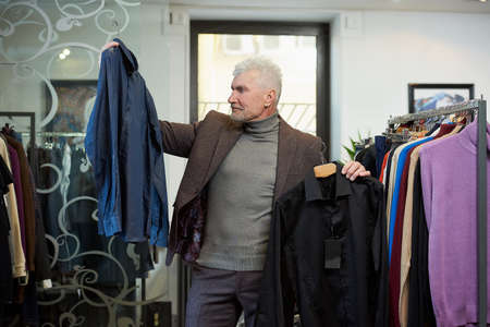 A mature man with gray hair and a sporty physique is choosing between two shirts in a clothing store. A male customer with a beard wears a wool suit in a boutique. Stock Photo
