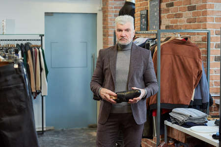A mature man with gray hair and a sporty physique is holding a black shoe in a clothing store. A male customer with a beard wears a wool suit in a boutique.