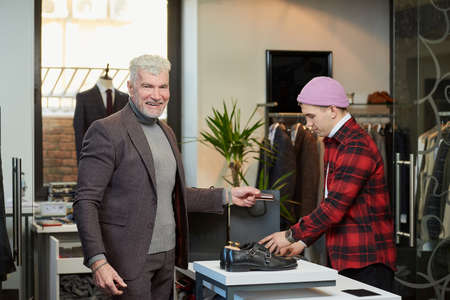 A smiling mature man with gray hair and a sporty physique is holding a credit card in a clothing store. A male customer with a beard and a shop assistant in a boutique.