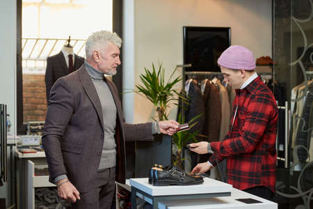 A mature man with gray hair and a sporty physique is handing a credit card to a seller to pay for purchases in a clothing store. A male customer with a beard and a shop assistant in a boutique. Stock Photo