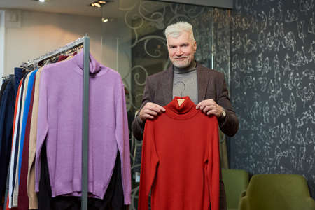 A happy mature man with gray hair and a sporty physique is showing a red turtleneck sweater in a clothing store. A male customer with a beard wears a wool suit in a boutique.