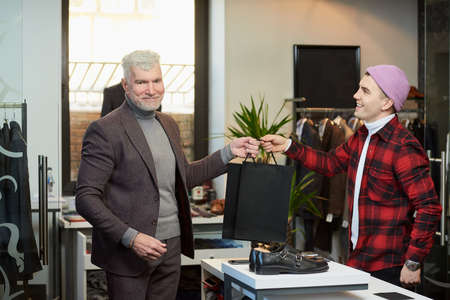 A mature man with gray hair and a sporty physique is taking black paper bags with purchases from a seller in a clothing store. A shop assistant with a smile is giving paper bags to a male customer. Stock Photo