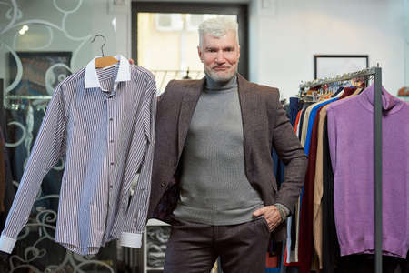A mature man with gray hair and a sporty physique is posing and showing a shirt in a clothing store. A male customer with a beard wears a wool suit in a boutique. Stock Photo