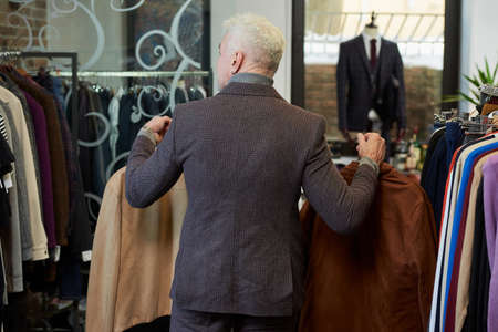 A photo from behind of a mature man with gray hair and a sporty physique is going with two jackets to the fitting room in a clothing store. A male customer with a beard wears a wool suit in a boutique