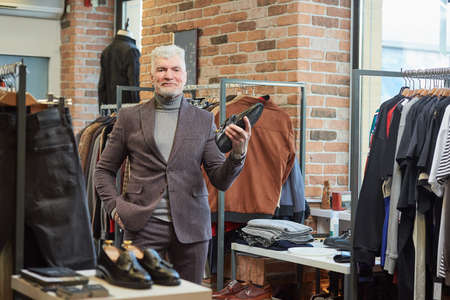 A happy mature man with gray hair and a sporty physique is posing holding a black shoe in a clothing store. A male customer with a beard wears a wool suit in a boutique Stock Photo