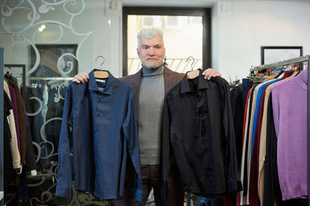 A mature man with gray hair and a sporty physique is posing and showing two shirts in a clothing store. A male customer with a beard wears a wool suit in a boutique.
