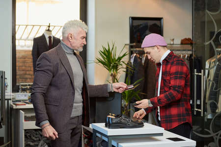 A mature man with gray hair and a sporty physique is handing a credit card to a seller to pay for a purchase in a clothing store. A male customer with a beard and a shop assistant in a boutique. Stock Photo