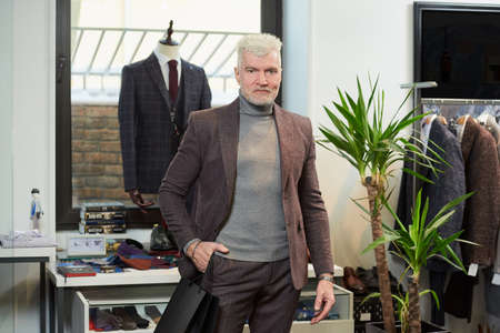 A happy mature man with gray hair and a sporty physique is posing with his purchases in black paper bags in a clothing store. A male customer with a beard wears a wool suit in a boutique