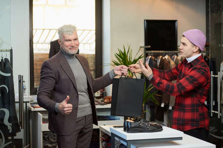A mature man with gray hair and a sporty physique is taking black paper bags from a seller and showing thumbs up in a clothing store. A shop assistant is giving paper bags to a male customer. Stock Photo