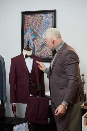A mature man with gray hair and a sporty physique is examining a wool suit on a mannequin in a clothing store. A male customer with a beard in a boutique Stock Photo
