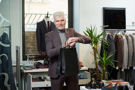 A happy mature man with gray hair and a sporty physique is staring at his wristwatch holding two black paper bags in a clothing store. A male customer with a beard wears a wool suit in a boutique