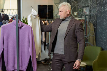A mature man with gray hair and a sporty physique is choosing a turtleneck sweater in a clothing store. A male customer in a wool suit in a boutique. Stock Photo
