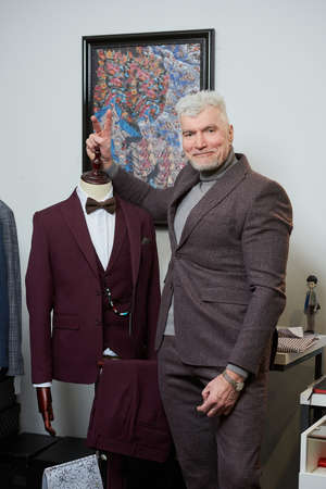A happy mature man with gray hair and a sporty physique is fooling around near a mannequin in a clothing store. A male customer with a beard wears a suit in a boutique.
